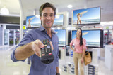 Portrait of smiling man holding remote control in front of televisions in electronics store