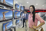 Portrait of smiling woman looking at flat screen televisions in electronics store