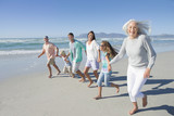 Portrait of happy multi-generation family holding hands and running on sunny beach