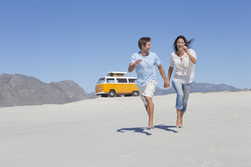 Happy couple holding hands and running on beach with van in background
