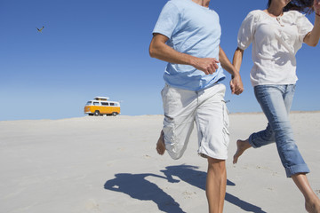 Couple holding hands and running on beach with van in background