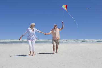 Happy senior couple holding hands and flying kite on sunny beach