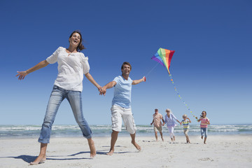 Happy family with kite running on sunny beach