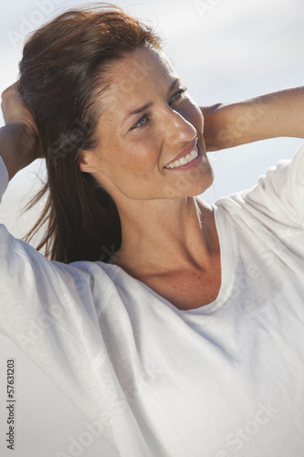 Close up of smiling woman with hands in hair