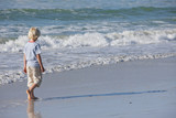 Boy walking in surf on sunny beach