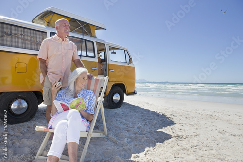 Senior couple relaxing outside van on sunny beach