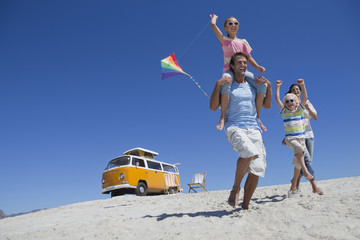 Happy family with kite walking on sunny beach with van in background