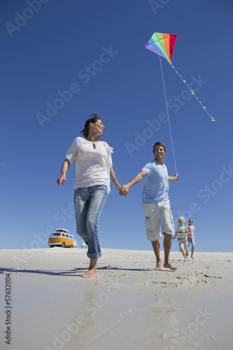 Family with kite running on sunny beach with van in background