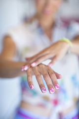 Portrait of woman showing off flower design on manicured fingernails