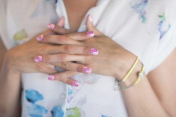 Close up of woman with flower design on manicured fingernails