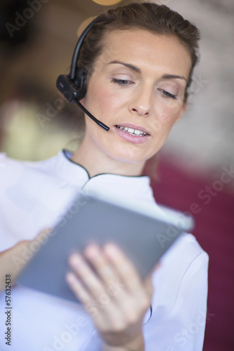 Close up of beautician with digital tablet talking on the phone with headset