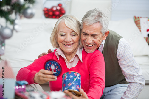 Happy Senior Couple Looking At Christmas Gift