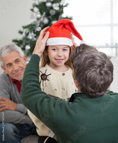 Father Adjusting Girl's Santa Hat