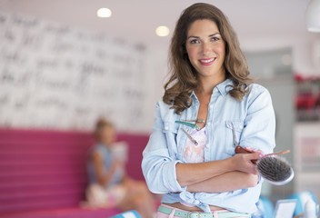 Portrait of confident hairdresser holding hairbrush at salon