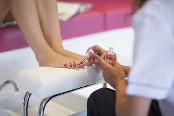 Nail technician applying fingernail polish to woman's toenails in nail salon