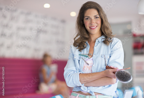 Portrait of confident hairdresser holding hairbrush at salon
