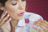 Woman blowing on freshly painted fingernails