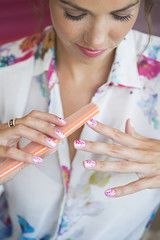 Close up of woman filing fingernails with flower design