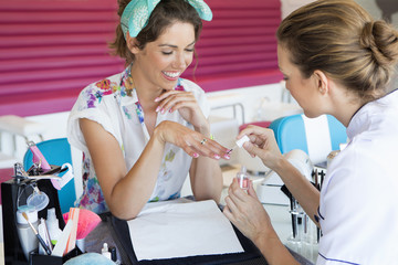 Nail technician applying fingernail polish to woman's fingernails in nail salon