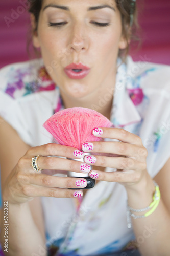 Woman with flower design on manicured fingernails blowing brush