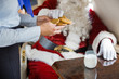 Stewardess Serving Cookies To Santa In Private Jet