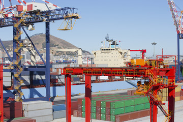 Cranes, container ship and cargo containers at commercial dock