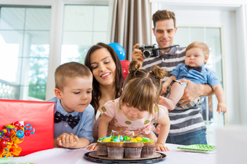 Family Watching Girl Blowing Out Candles On Birthday Cake