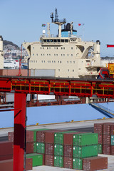 Crane, container ship and cargo containers at commercial dock