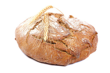Loaf of rye bread and wheat ears.