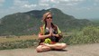 A girl sits in a lotus position on top of a mountain.