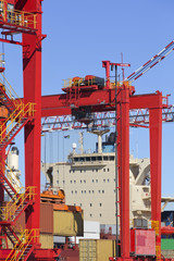 Cranes and cargo containers alongside moored container ship at commercial dock