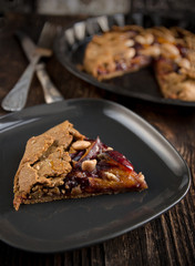 Whole-grain cereal biscuit with plums on the wood background