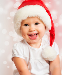 Beautiful funny baby in a Christmas hat  on pink