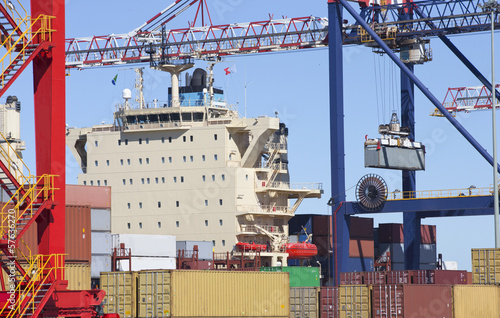 Crane lifting cargo container alongside container ship at commercial dock