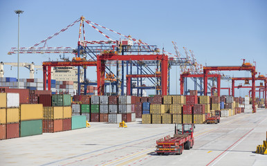 Cranes and cargo containers alongside container ship moored at commercial dock