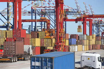 Cranes loading cargo containers onto trucks at commercial dock