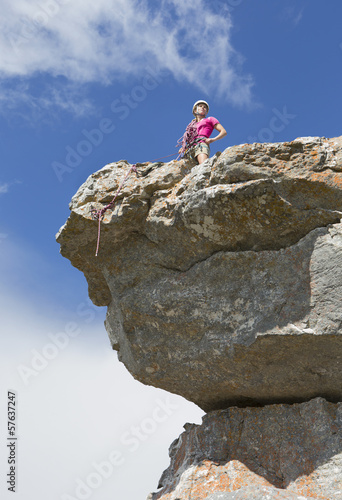 Female rock climber on top of rock with hands on hips