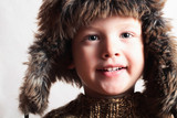 smiling child in a fur hat.fashion boy.winter style.children