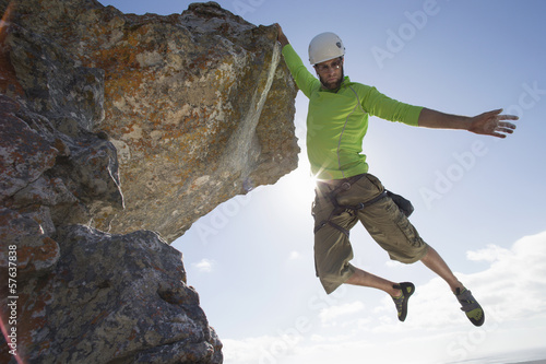 Male rock climber hanging from rock with arm outstretched