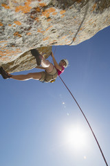 Sun shining above female rock climber abseiling down rock face