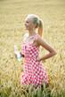 Junge blonde Frau geht durch ein Kornfeld