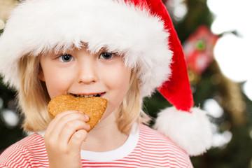 Boy in Santa hat eating gingerbread
