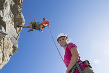 Portrait of woman looking at camera as male rock climber is abseiling down rock face