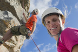 Portrait of smiling woman looking at camera as male rock climber is abseiling down rock face