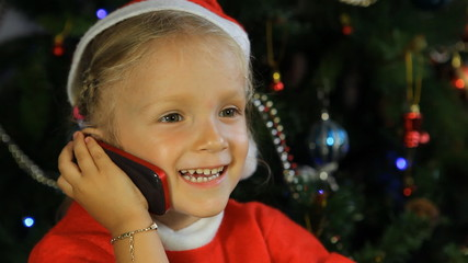 Laughing Child in Santa Claus Talking on Phone by Christmas Tree