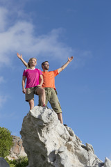 Rock climbers standing on top of rock with arms outstretched