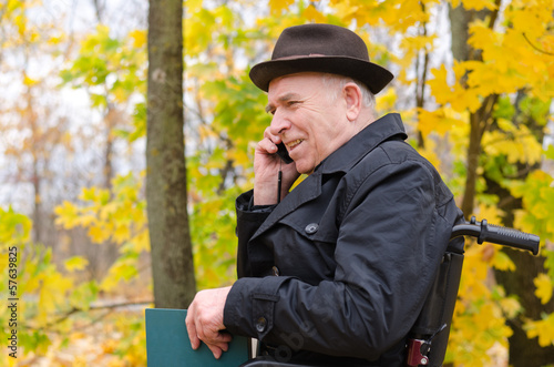 Senior man in a wheelchair chatting on his mobile
