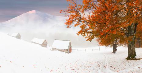 Colorful autumn sunset in the mountains. First snow in November