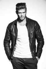 fashion model in leather jacket with hands in his pockets