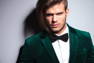 man with long hair wearing an elegant green suit and neck bow t